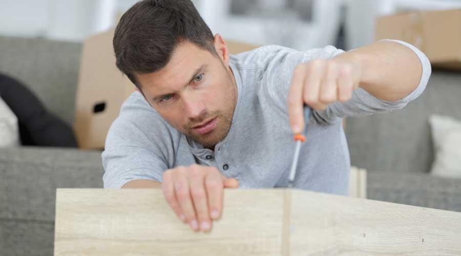 man dismantling disassembling furniture